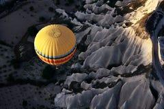 Een hete luchtballon vliegt boven het spectaculaire Cappadocia-landschap bij zonsopgang Royalty-vrije Stock Foto's