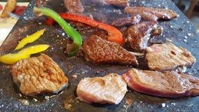 Een hete steen met gesneden rundvlees, kip en eend en sommige kleurrijke groenten royalty-vrije stock afbeelding