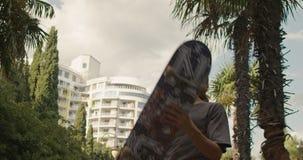 Een hipsterkerel met krullend haar gaat langs de steeg met palmen en draaien en werpt een vleet in zijn handen Langzame Motie stock footage
