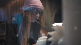 Een hipsterwijfje in modieuze glazen en hoedenzitting in koffie en het werken met laptop Mening door het Venster stock videobeelden