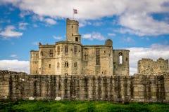 Een historisch kasteel met een vlag van northumberland stock fotografie