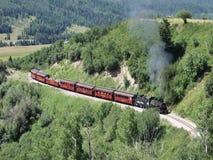 Een historische steenkool gevoede passagierstrein die zijn manier wending door een bergpas
