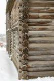 Een hoek van de houten logboekmuur op de sneeuwachtergrond royalty-vrije stock fotografie