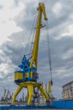 Een hoge havenkraan in blauw en geel tegen de achtergrond van een dramatische hemel Royalty-vrije Stock Foto's