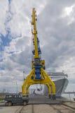 Een hoge havenkraan in blauw en geel tegen de achtergrond van een dramatische hemel en een groot wit schip Stock Fotografie