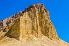 Een hoge onvruchtbare piek van de woestijnberg met steile hellingen in gouden tinten stock afbeelding