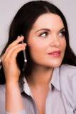 Mooi jong wijfje die op een apparaat van iPhonesmartphone spreken royalty-vrije stock fotografie