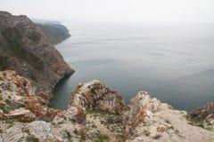 Een hoge rotsachtige kustlijn een klip in het overzees een meer en een mist over het water royalty-vrije stock fotografie