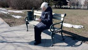 Een hogere bejaardezitting op een bank in park in openlucht en gebruikend onttrekkend smartphone - zij gebruikt smartphone aan stock video
