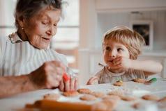 Een hogere grootmoeder met het kleine peuterjongen maken koekt thuis stock foto's
