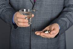 Een hogere mens die geneeskunde met een glas water nemen Royalty-vrije Stock Afbeeldingen
