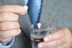 Een hogere mens die geneeskunde met een glas water nemen Stock Fotografie