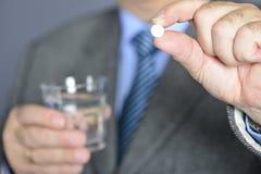 Een hogere mens die geneeskunde met een glas water nemen Royalty-vrije Stock Foto
