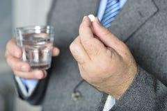 Een hogere mens die geneeskunde met een glas water nemen Royalty-vrije Stock Afbeelding