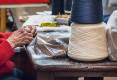 Een hogere naaistersvrouw die met haar handen naaien een kledingstuk in haar workshop met rol past in Ancona in , Italië stock afbeelding