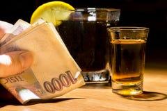 Een holdingsbankbiljetten van de mensen` s hand bij een bar stock fotografie