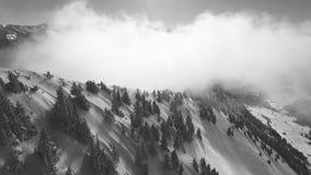 Een hommelvlucht in de Zwitserse bergen door de mist stock videobeelden