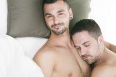 Een homoseksueel paar onder een bed in studiowit royalty-vrije stock fotografie