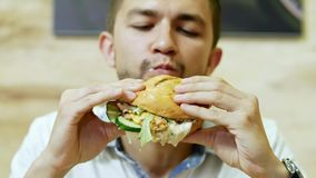 Een hongerige mens die een sappige hamburger in een snel voedselrestaurant eten, heerlijk voedsel stock video