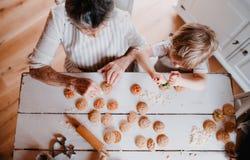 Een hoogste mening van hogere grootmoeder met het kleine peuterjongen maken koekt thuis stock afbeeldingen