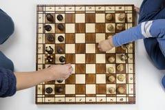 een hoogste mening van een kind en een volwassen het spelen schaak op witte backgr stock fotografie