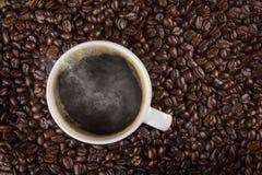 Een hoogste mening van een kop van hete koffie op een houten lijst met geroosterde koffiebonen Stock Foto's