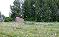 Een hooiberg dichtbij boomgaard, mooi landelijk landschap op een bewolkte dag stock fotografie