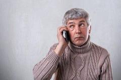 Een horizontaal portret van de rijpe mens met grijs haar en rimpels kleedde zich in warme sweater houdend mobiele telefoon op zij stock foto