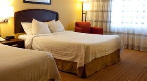 Een hotelruimte met bedden, stoel en lampen Stock Afbeeldingen