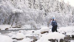 Een houdend van paar in een de winterbos werpt stenen bij een stroom die door een mooi landschap vloeit stock video