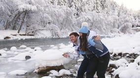 Een houdend van paar in een de winterbos werpt stenen bij een stroom die door een mooi landschap vloeit stock footage