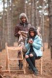 Een houdend van paar in het bos, een kerel verbergt het meisje met een deken, drinkt het meisje thee outdoors stock afbeeldingen
