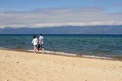 Een houdend van paar van een man en een vrouw loopt langs de zandkustlijn van Meer Baikal op een bergachtergrond op een zonnige d royalty-vrije stock afbeelding
