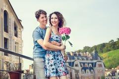 Een houdend van paar omhelst en lacht gelukkig tegen de achtergrond van een oude straat en een duidelijke hemel Het meisje in de  royalty-vrije stock foto