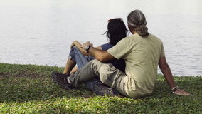 Een houdend van paar zit door Meer bekijkend het water stock video