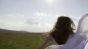 Een houdt de gelukkige meisjeslooppas over het gebied en een witte zakdoek in haar hand stock video