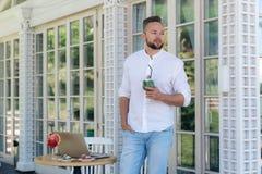 Een houdt de modieuze aantrekkelijke mensentribunes in een koffie, een glas van muntcocktail in zijn hand, stylishly gekleed in e royalty-vrije stock foto