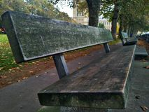 Een houten bank op de bank van de rivier Theems Londen, Groot-Brittannië royalty-vrije stock foto