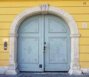Een houten deur op een gele muur stock foto's