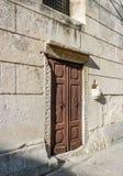 Een houten die deur met steenrand en kruisen in het steenwerk worden gekrast stock afbeeldingen