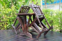Een houten die eettafel in het weelderige tuin plaatsen wordt geplaatst Royalty-vrije Stock Fotografie