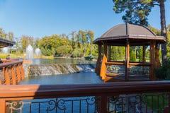 Een houten die gazebo met lampen in de schaduw van de pijnboom, boven het meer dichtbij de fontein wordt geplaatst Mezhygirya de  Stock Fotografie
