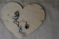 Een houten hart voor de Dag van Valentine ` s met zilveren ornamenten, kettingen met diamanten en edelstenen Stock Fotografie