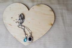 Een houten hart voor de Dag van Valentine ` s met zilveren ornamenten, kettingen met diamanten en edelstenen Royalty-vrije Stock Afbeeldingen