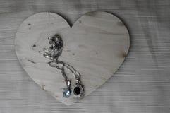 Een houten hart voor de Dag van Valentine ` s met zilveren ornamenten, kettingen met diamanten en edelstenen Stock Afbeelding