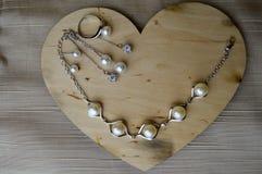 Een houten hart voor de Dag van Valentine ` s met zilveren ornamenten, oorringen, ringen, halsbanden met parels, diamanten, edels Stock Afbeeldingen