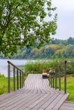 Een houten het lopen weg met leuningen in park op de rivierkust stock fotografie