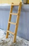 Een houten ladder die tegen muur leunen royalty-vrije stock foto