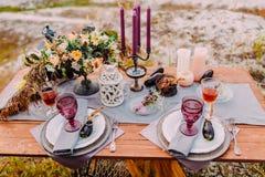 Een houten lijst wordt gediend voor twee, op de lijst zijn er samenstellingen van bloemen, kaarsen, bestek en glazen voor wijn royalty-vrije stock foto