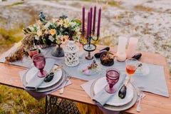 Een houten lijst wordt gediend voor twee, op de lijst zijn er samenstellingen van bloemen, kaarsen, bestek en glazen voor wijn stock afbeelding